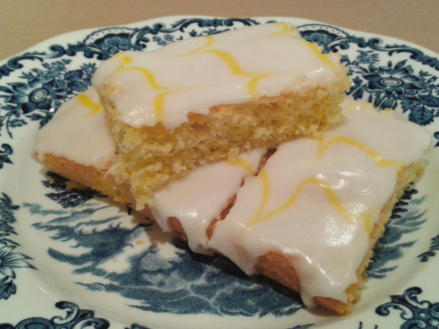 Lemon sponge cake with white icing and yellow feathered icing sliced 4